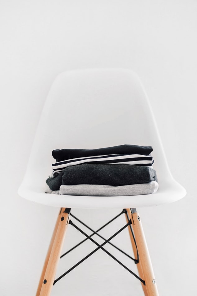 folded clothes on a white chair